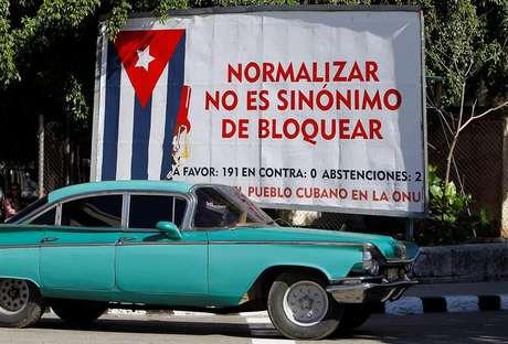 Havana: carro antigo passa em frente a cartaz alusivo ao bloqueio econômico imposto pelos Estados Unidos a Cuba