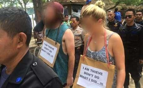 """Recentemente, dois turistas tiveram que desfilar pelas ruas da ilha Gili T com cartazes dizendo: """"Sou ladrão. Não faça o que eu fiz..!""""; A foto foi divulgada na página da ilha indonésia no Facebook"""