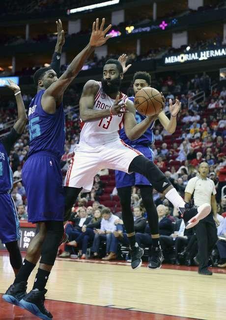 James Harden, base de los Rockets de Houston, envía un pase entre Roy Hibbert (55) y Jeremy Lamb, de los Hornets de Charlotte