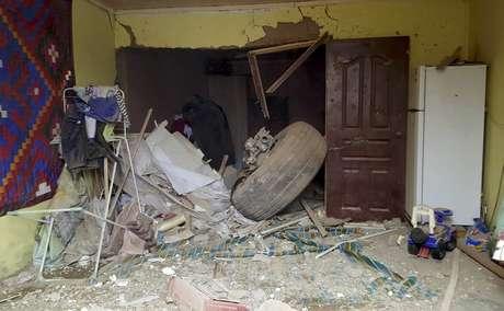 Uma das rodas do avião foi parar dentro de uma casa após a queda da aeronave no Quirguistão.