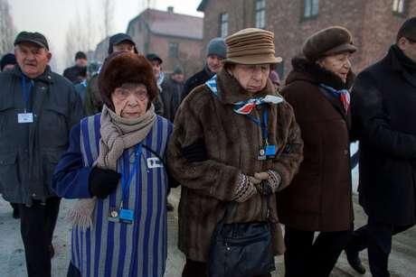 Sobreviventes caminham pelo campo de Auschwitz