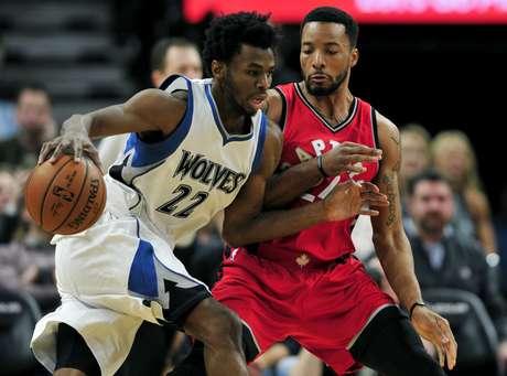 Andrew Wiggins, alero de los Timberwolves de Minnesota, conduce el balón frente a Norman Powell, de los Raptors de Toronto