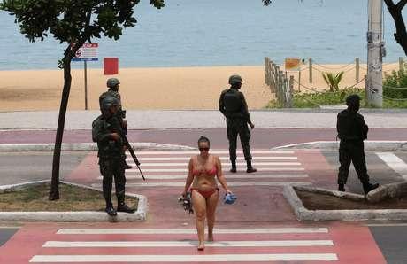 Mulher deixa a praia no litoral de Vitória cuja a segurança é feita por homens do Exército.