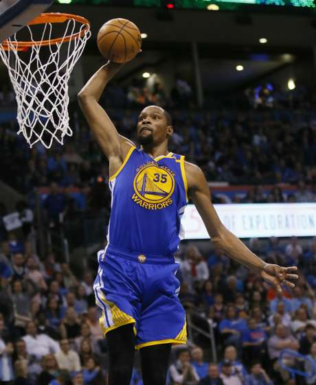 El jugador de los Warriors de Golden State Kevin Durant (35) salta para hacer un mate en el segundo cuarto de su juego NBA contra el Thunder de Oklahoma City en Oklahoma City