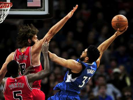 Karl-Anthony Towns (32) de los Timberwolves de Minnesota dispara al aro sobre Bobby Portis (5) y Robin López (8) de los Bulls de Chicago, el domingo 12 de febrero de 2017