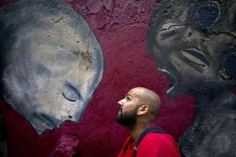 En esta foto del 9 de febrero de 2017 el artista de graffiti Yulier Rodríguez Pérez posa con una de sus obras pintada en una pared de La Habana Vieja, Cuba.