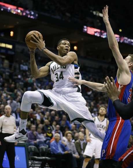 Giannis Antetokounmpo (34) de los Bucks de Milwaukee busca pasar el balón ante Jon Leuer de los Pistons de Detroit