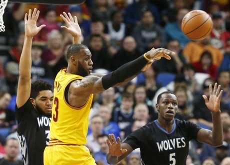LeBron James de los Cavaliers de Cleveland pasa el balón ante Karl-Anthony Towns (izquierda) y Gorgui Dieng de los Timberwolves de Minnesota
