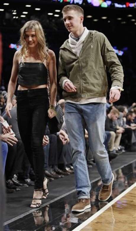 Genie Bouchard, camina hacia la cancha con su cita a ciegas, John Goehrke, a la derecha, durante la primera mitad del juego entre los Nets de Brooklyn y los Bucks de Milwaukee el miércoles 15 de febrero de 2017 en Nueva York. Luego de perder una apuesta del Super Bowl en Twitter, Bouchard accedió a salir en una cita con un seguidor