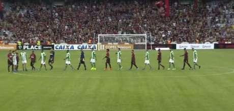Jogadores de Coxa e Furacão entraram no gramado, misturados e de mãos dadas, e foram aplaudidos pelos torcedores. (Foto: Reprodução)
