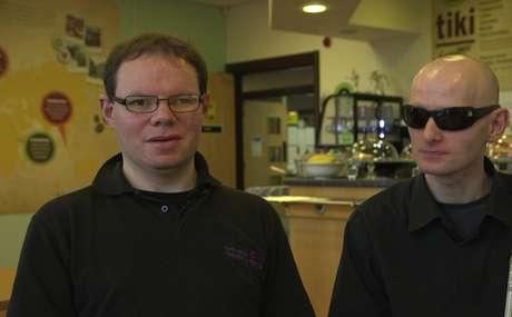 Dupla trabalha em café na Escócia; Peter guia David pela cozinha e toma conta para que este não se corte ou queime.