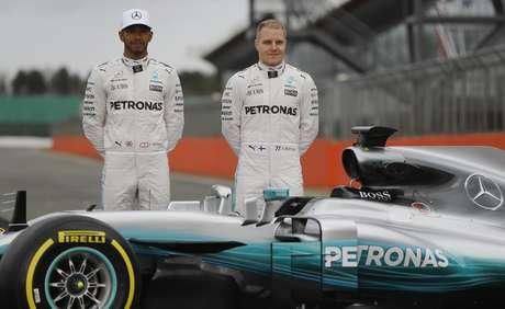 Los pilotos de Mercedes, Lewis Hamilton, izquierda, y Valtteri Bottas posan con el vehículo de la escudería para la temporada de 2017 de la Fórmula Uno el jueves, 23 de febrero de 2017, en Towcester, Inglaterra