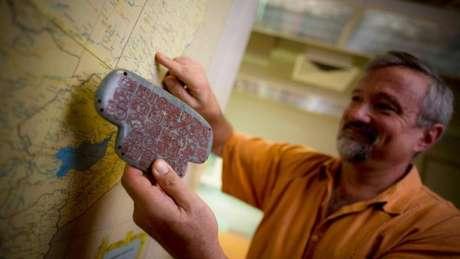 Geoffrey Braswell, arqueólogo da Universidade da Califórnia, segura uma réplica do pingente