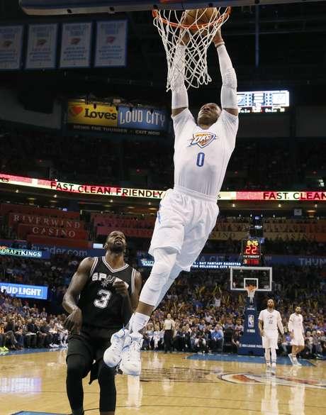 El base Russell Westbrook (0), del Thunder de Oklahoma City, clava el balón ante la mirada del pivote Dewayne Dedmon, de los Spurs de San Antonio