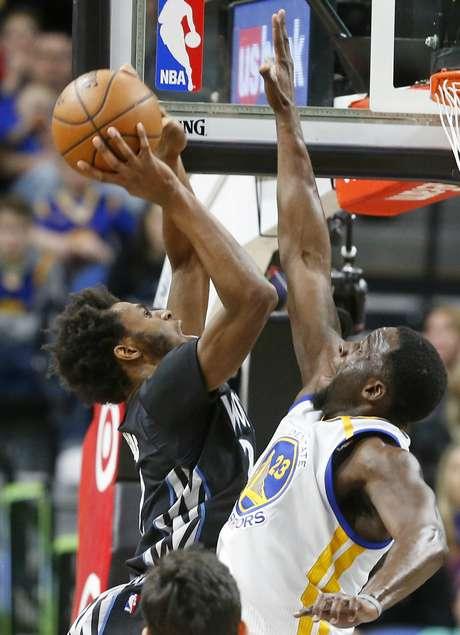 Andrew Wiggins, izquierda, de los Timberwolves de Minnesota, intenta encestar sobre Draymond Green, de los Warriors de Golden State, en la segunda mitad del juego del viernes 10 de marzo de 2017, en Minneapolis