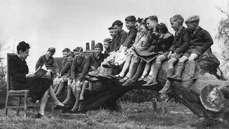 Professora lê para um grupo de crianças em Stevenage, antes de serem enviadas à fazenda de Fairbridge, em Molong.