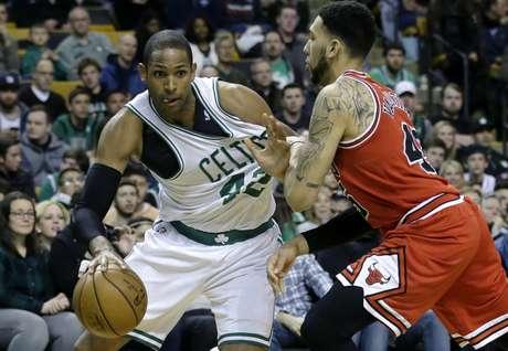 El dominicano Al Horford, de los Celtics de Boston, a la izquierda, intenta pasar a Denzel Valentine, de los Bulls de Chicago, en el primer periodo del partido de la NBA en Boston, el domingo 12 de marzo de 2017