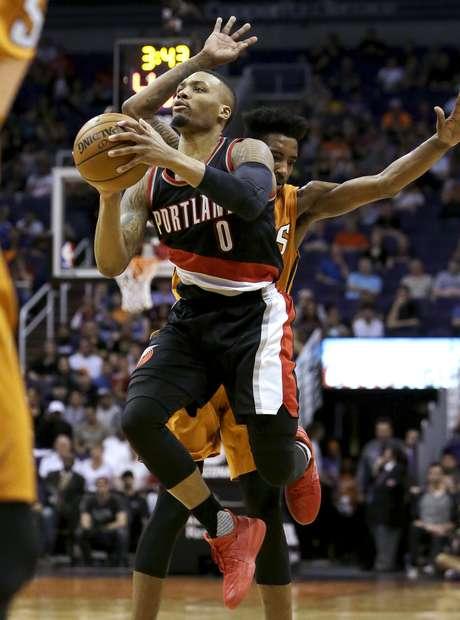 Damian Lillard, base de los Trail Blazers de Portland, recibe una falta de Marquese Chriss, de los Suns de Phoenix, durante el segundo cuarto del encuentro del domingo 12 de marzo de 2017