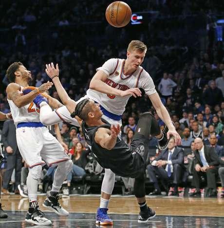 Jeremy Lin (7), de los Nets de Brooklyn, al frente, es derribado por Kirstaps Porzingis (69), de los Knicks de Nueva York