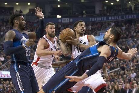 DeMar DeRozan (10) de los Raptors de Toronto es víctima de una falta cometida por Salah Mejri (50) de los Mavericks de Dallas, el lunes 13 de marzo de 2017. Wesley Matthews (23) de Dallas y Jonas Valanciunas (17) de Toronto observan