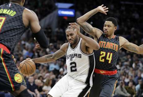 Kawhi Leonard, de los Spurs de San Antonio, dribla a Kent Bazemore (24), de los Hawks de Atlanta