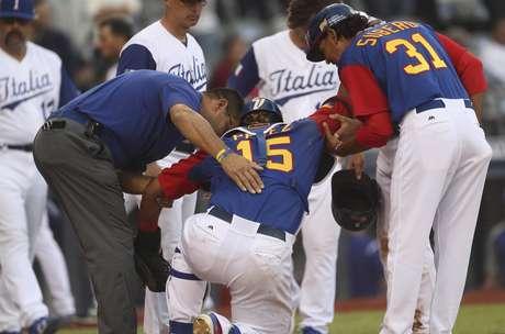 El cátcher de Venezuela, Salvador Pérez, centro, es ayudado a ponerse de pie tras sufrir una colisión en el plato en un partido contra Italia por el Clásico Mundial de Béisbol el sábado, 11 de marzo de 2017, en Guadalajara, México.