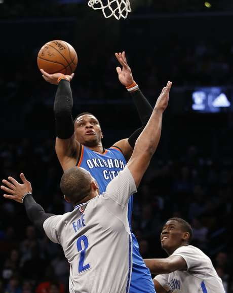 Russell Westbrook, del Thunder de Oklahoma City, dispara frente a Randy Foye, de los Nets de Brooklyn