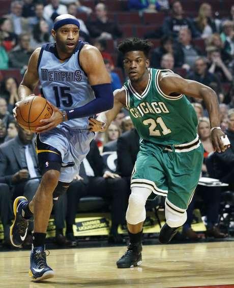 Vince Carter, izquierda, de los Grizzlies de Memphis, se enfila a la canasta ante la marca de Jimmy Butler, de los Bulls de Chicago, en el duelo del miércoles 15 de marzo de 2017, en Chicago