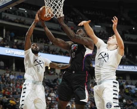 Brandon Bass, de los Clippers de Los Ángeles, prepara un enceste entre Will Barton, izquierda, y Nikola Jokic, de los Nuggets de Denver