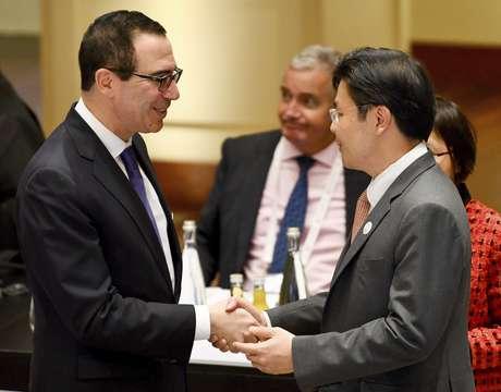 El secretario del Tesoro de Estados Unidos, Steven Mnuchin, a la izquierda, estrecha la mano de Lawrence Wong, ministro singapurense de Desarrollo Nacional, en la cumbre de ministros de Finanzas del g20 en Baden-Baden, en el sur de Alemania, el viernes 17 de marzo de 2017.