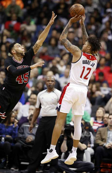 Kelly Oubre, de los Wizards de Washington, dispara frnete a Denzel Valentine, de los Bulls de Chicago, en el duelo del viernes 17 de marzo de 2017