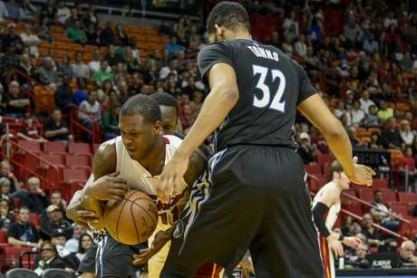 Dion Waiters, del Heat de Miami, disputa un balón ante el dominicano-estadounidense Karl Anthony Towns, de los Timberwolves de Minnesota