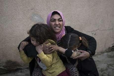 Fotografía del martes 14 de marzo de 2017 de una mujer cubriendo a sus hijas mientras se escuchan disparos en un barrio recién liberado por las fuerzas de seguridad iraquíes en Mosul, Irak.