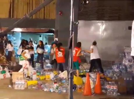 Korina Rivadeneira en polo blanco ayudando con la donaciones.