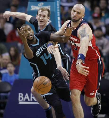 Michael Kidd Gilchrist (izquierda) y Cody Zeller, de los Hornets de Charlotte, disputan un balón suelto con Marcin Gortat, de los Wizards de Washington