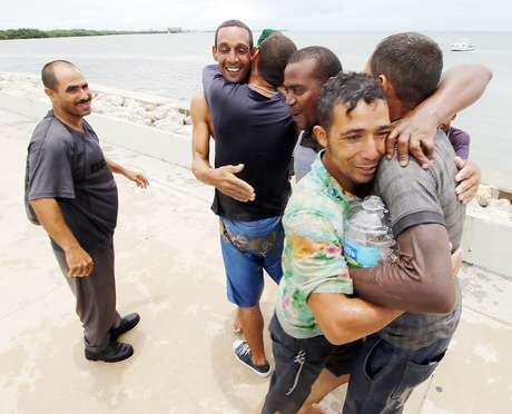 """ARCHIVO- En esta fotografía de este archivo del 21 de junio de 2016 un grupo de hombres cubanos se abrazan al llegar a Key West, Florida. Unos 65 inmigrantes cubanos han sido interceptados en el mar desde el fin de la política de """"pies mojados y pies secos""""."""