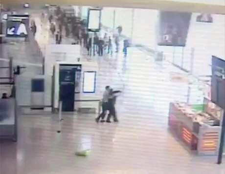Foto tomada del video obtenido por la AP que muestra el momento en que un presunto extremista islámico deja caer una bolsa de compras y ataca por detrás a una soldado en el aeropuerto de Orly, cerca de París, el sábado 18 de marzo del 2017. (Video obtenido de las cámaras de vigilancia, entregado a la AP con la condición de no revelar su fuente).