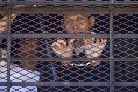 Un rehén que se identificó como un celador de la cárcel habla con periodistas mientras está esposado y rodeado de reclusos durante un motín en el Centro Correccional Etapa II en San José Pinula, Guatemala, el lunes 20 de marzo de 2017.