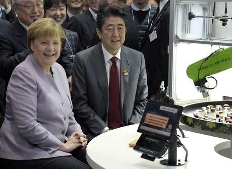 La canciller alemana Angela Merkel, izquierda, y el primer ministro japonés, Shinzo Abe, derecha, aparecen en la convención de tecnología CeBIT en Hanover, Alemania, el lunes 20 de marzo del 2017. Merkel está resaltando que Alemania no debe grandes cantidades de dinero a la OTAN por invertir menos de lo debido en defensa - alegato hecho por el presidente Donald Trump.