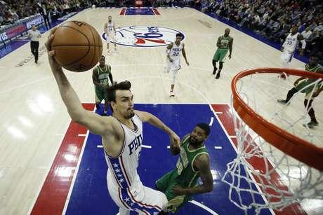 Dario Saric (izquierda) de los 76ers de Filadelfia se eleva para anotar ante Amir Johnson de los Celtics de Boston, el domingo 19 de marzo de 2017