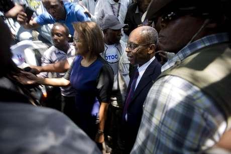 El ex presidente haitiano Jean-Bertrand Aristide, centro, camina junto a la ex candidata presidencial Maryse Narcisse afuera del palacio de justicia de Puerto Príncipe, Haití, el lunes 20 de marzo de 2017.