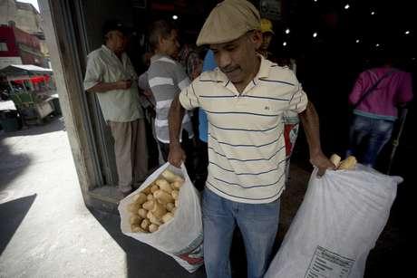 En esta imagen, tomada el 17 de marzo de 2017, un empleado de la panadería estatal Minka carga bolsas con pan para su distribución en tiendas estatales, en Caracas, Venezuela. Agentes de la Superintendencia Nacional para la Defensa de los Derechos Socioeconómicos (Sundde) irrumpieron en Mansion's Bakery la semana pasada y acusaron a los encargados de la panadería de acaparar la harina que les da el gobierno y que las autoridades exigen se use para elaborar pan y no productos más caros como pastelillos.