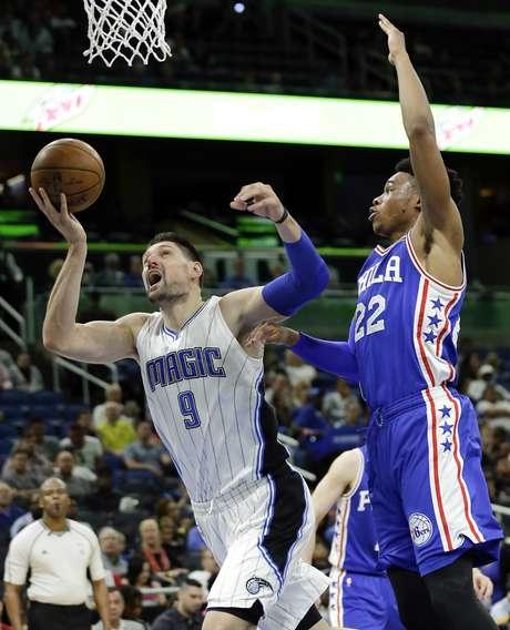 Nikola Vucevic (9) del Magic de Orlando es blanco de una falta de Richaun Holmes (22) de los 76ers de Filadelfia, el lunes 20 de marzo de 2017