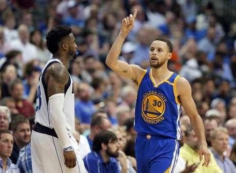 Stephen Curry, de los Warriors de Golden State, festeja luego de atinar un triple frente a Wesley Matthews, de los Mavericks de Dallas