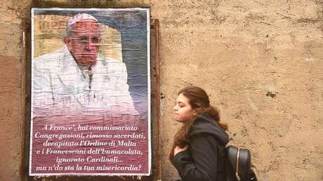 Mulher passa por cartaz com críticas ao papa Francisco