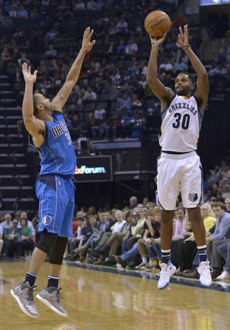 El base de los Grizzlies de Memphis Troy Daniels (30), intenta un triple ante el base Devin Harris (34), de los Mavericks de Dallas, en el juego de NBA del viernes 31 de marzo de 2017, en Memphis, Tennessee