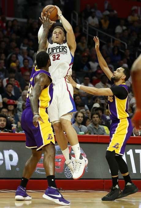 Blake Griffin de los Clippers de Los Angeles dispara frente a Tarik Black (izquierda) y Tyler Ennis (derecha) de los Lakers de Los Angeles, el sábado 1 de abril de 2017