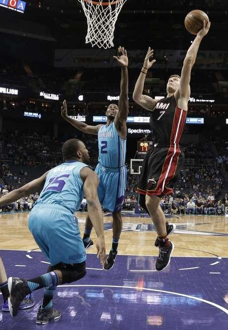 Goran Dragic (7), del Heat de Miami, intenta una canasta ante Marvin Williams (2) y Kemba Walker (15), de los Hornets de Charlotte, en el partido del miércoles 5 de abril de 2017 en Charlotte