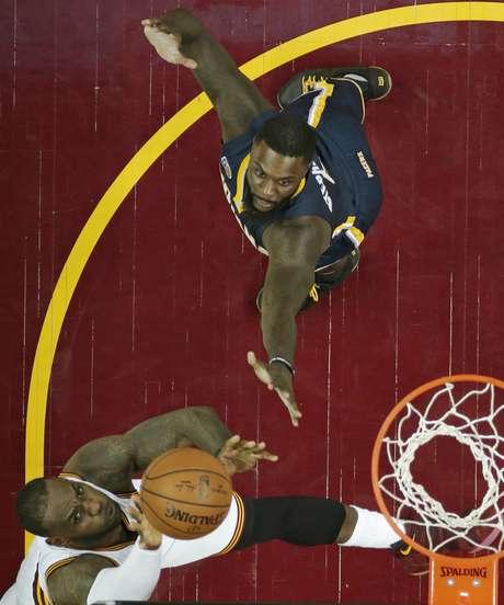 LeBron James (izquierda) de los Cavaliers de Cleveland penetra hacia la canasta ante Lance Stephenson de los Pacers de Indiana, el sábado 15 de abril de 2017