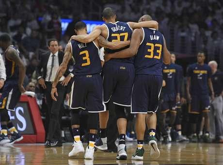 El jugador del Jazz de Utah Rudy Gobert (centro) recibe la ayuda de sus compañeros Boris Diaw (derecha) y George Hill (izquierda) para salir del campo tras una lesión de rodilla en el Juego 1 de los playoffs de la NBA que enfrentaron a su equipo con los Clippers de Los Ángeles, el 15 de abril de 2017, en Los Ángeles